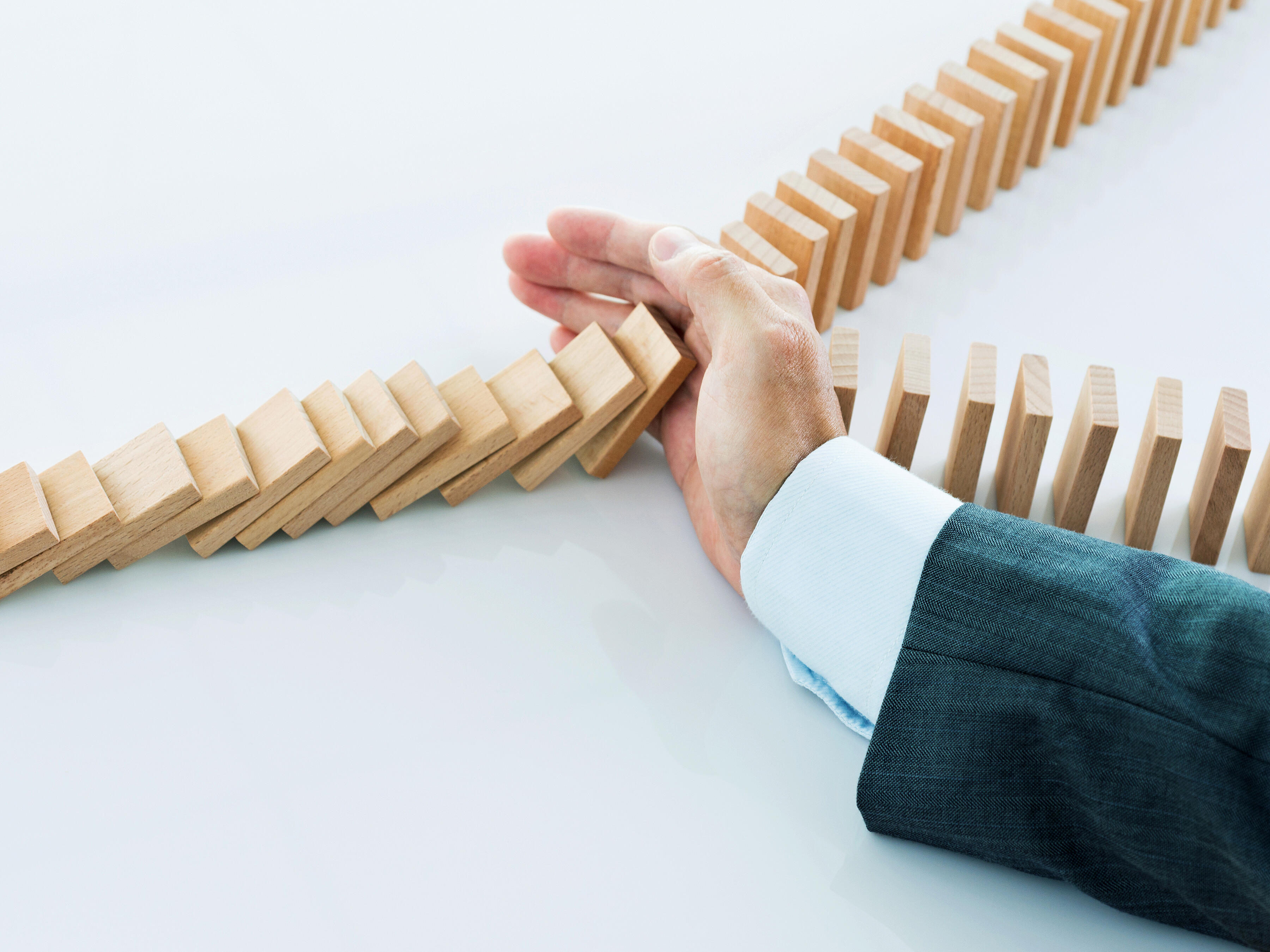 Business Man Stopping Falling Dominoes