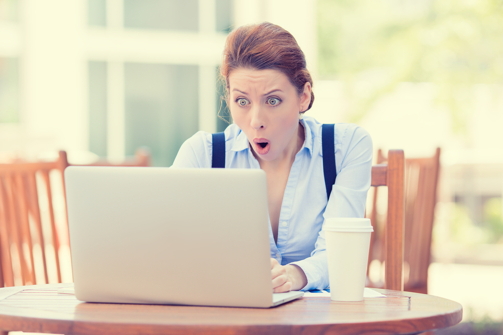 Shocked young business woman using laptop looking at computer screen blown away in stupor sitting outside corporate office. Human face expression, emotion, feeling, perception, body language, reaction-1